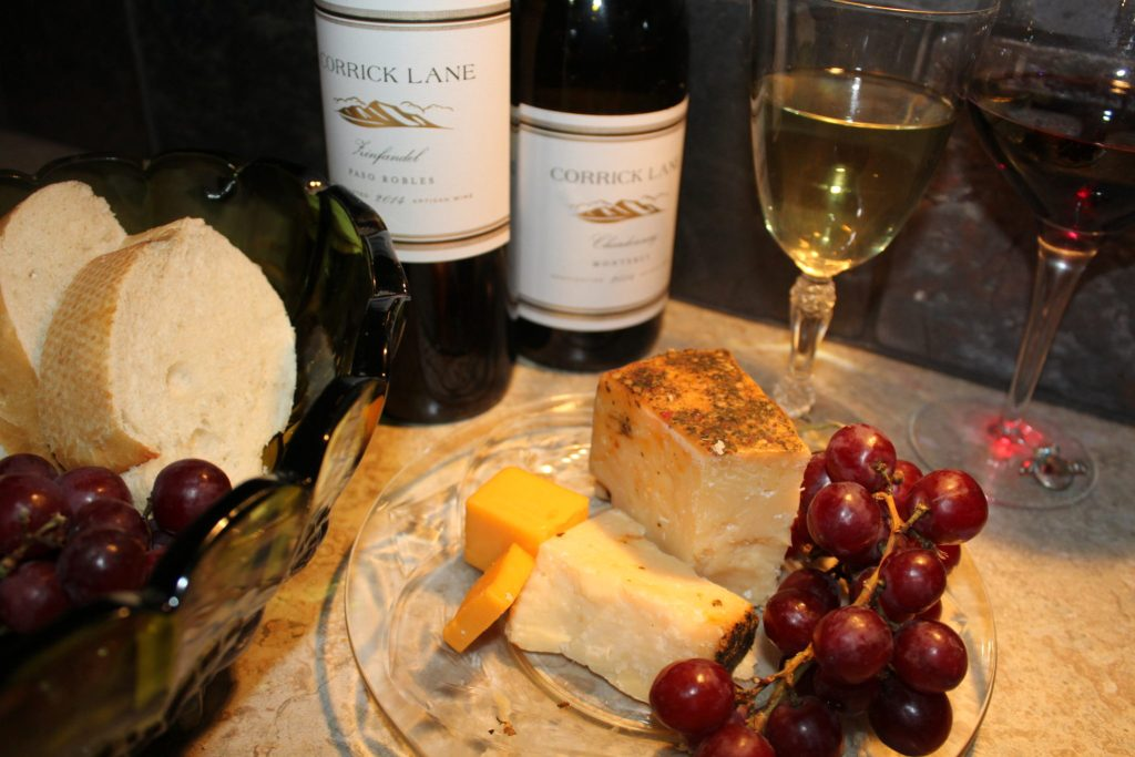 St. Urho's Day and Wine Club Review.Wine glasses and bottles with Chardonnay and Zinfandel, french bread, cheeses and grapes Wine Club featured