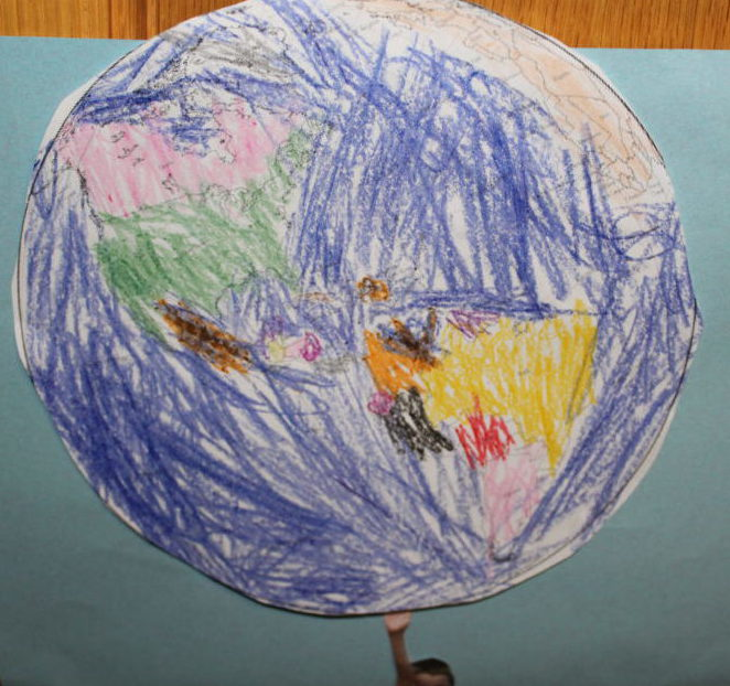 A child's artwork is a precious treasure. A child's drawing of Earth made with paper and crayons.
