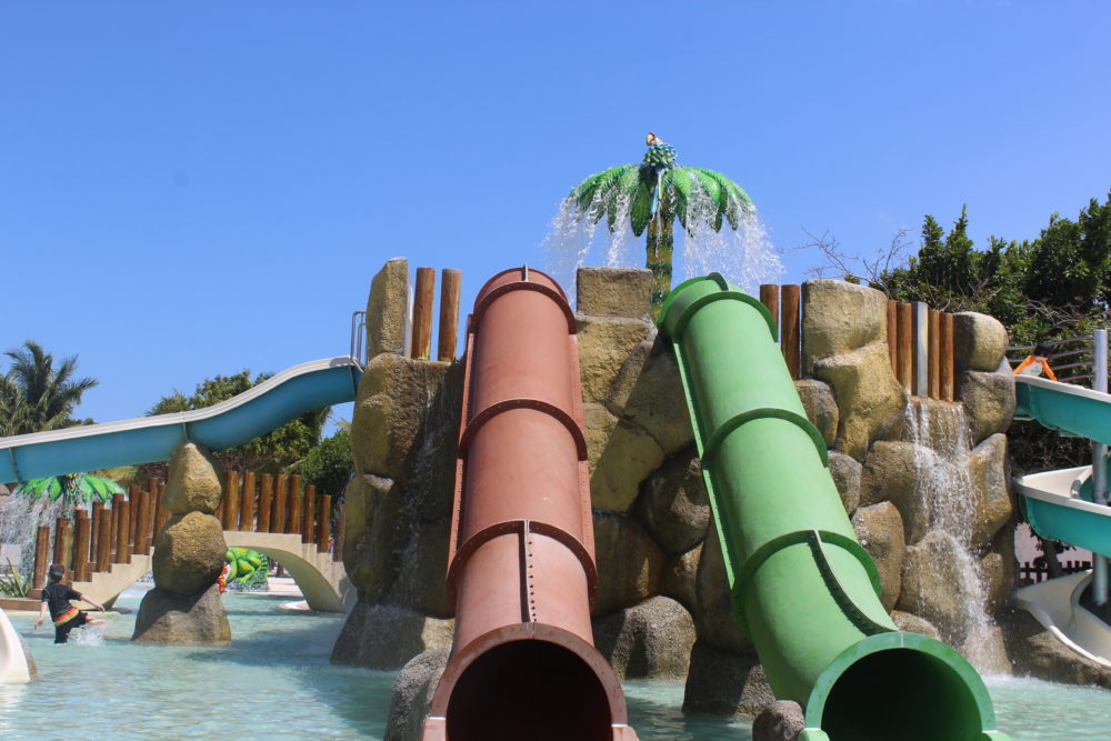Kids fun swimming pool area with slides for bigger kids and a frog slide for toddlers too. Palladium all-inclusive resorts in Riviera Maya, Mexico.