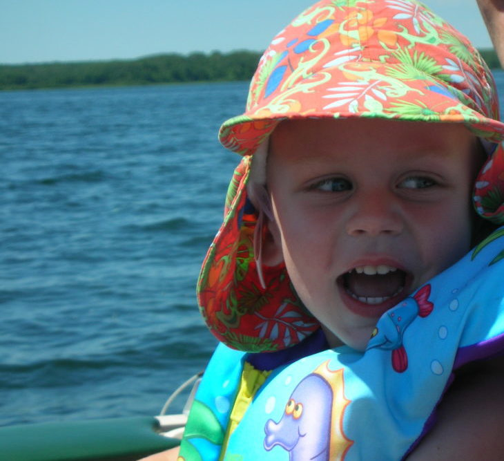 Toddler drives a boat and smiles