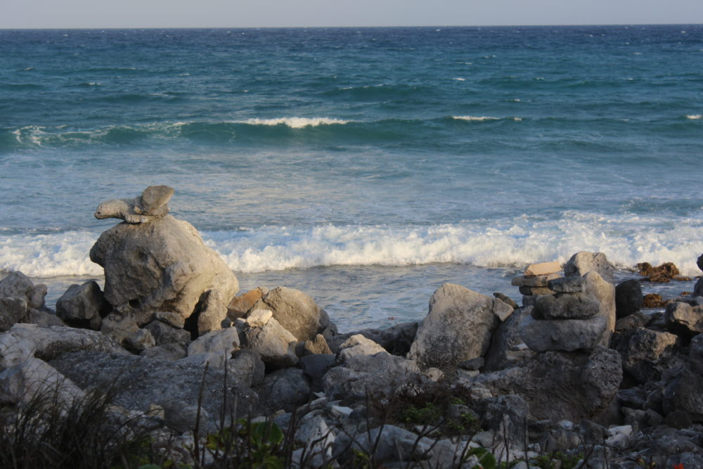 Rocky beach shoreline at large all-inclusive resort.