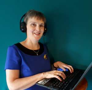 photo of Julie Millar in a blue dress, wearing headphones and using a laptop