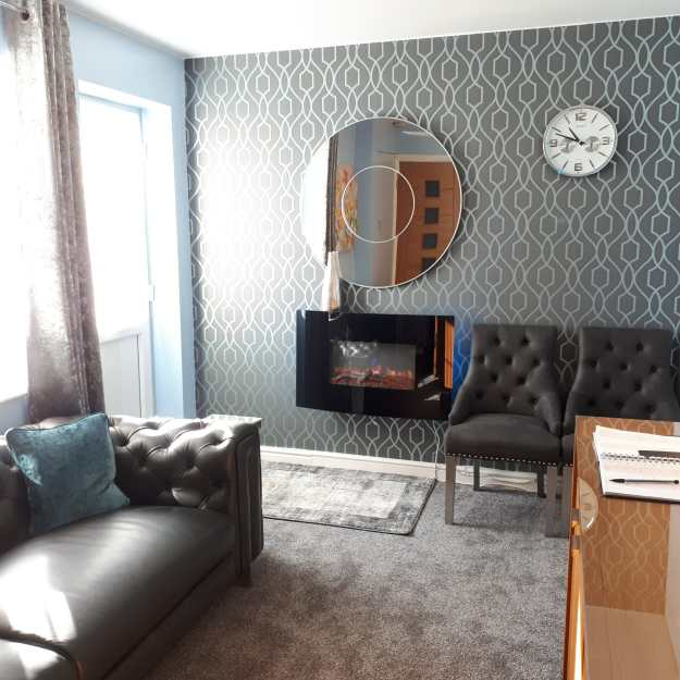 Upton waiting room showing sofa, chairs and mirror and clock on the wall