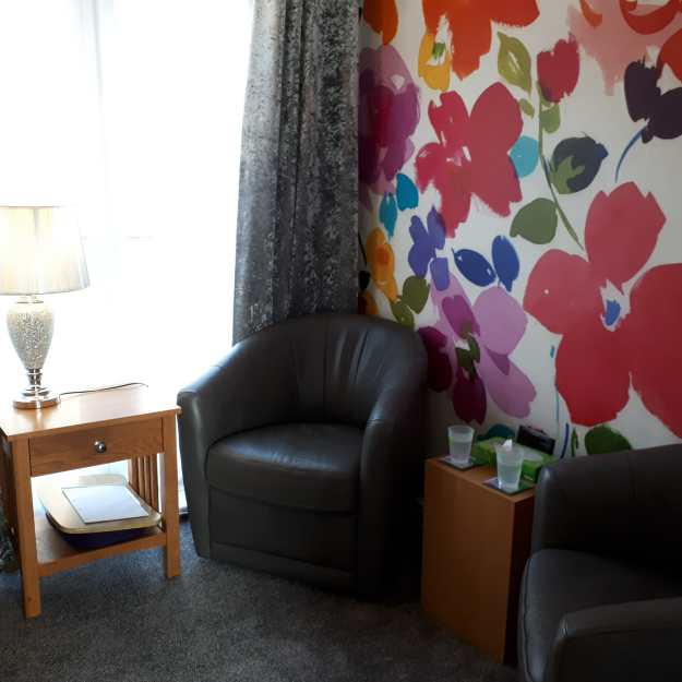 a cosy room with bucket chairs and bright wallpaper