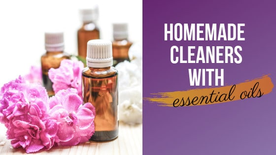 pink and white flowers on a white table with bottles of essential oils