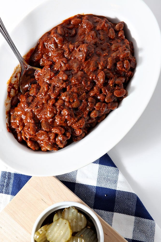 Overhead image of Instant Pot Baked Beans, shown in a white bowl, shown with a blue buffalo plaid napkin and a platter of barbecue sides