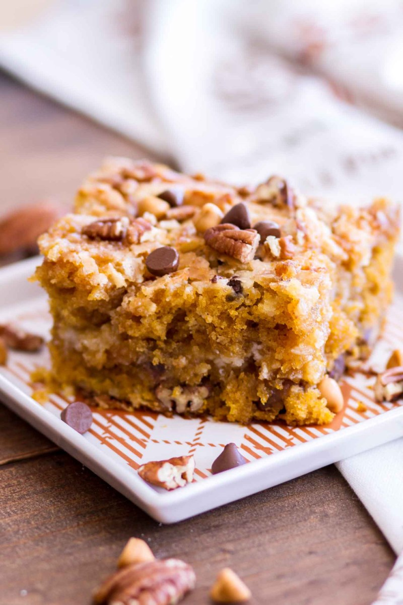 A serving of Pumpkin Earthquake Cake on a dish topped with chocolate and butterscotch chips and pecans.