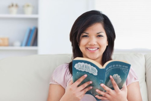 Woman smiling while holding a book in a living room