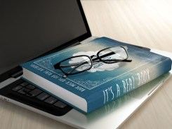 Laptop, green book and glasses on wooden desk. Electronic education concept.