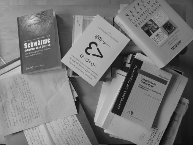 Hier sieht man ein Bild von verschiedenen Büchern und beschriebenen Zetteln
