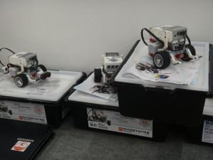 Hier sieht man einige Kisten mit Lego-Robotern, an denen die Kinder spielerisch experimentieren konnten