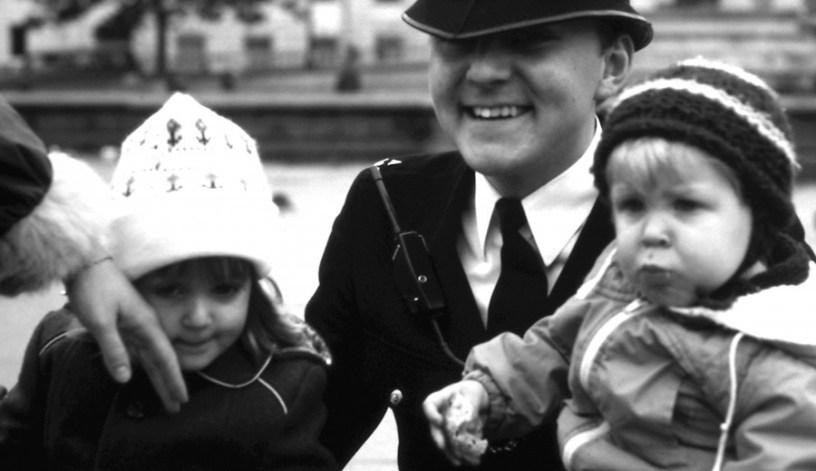 Mein Bruder und ich als ganz kleine Kinder auf dem Schoß eines englischen Bobbys, eines Polizisten. Links im Bild die Hand meiner Mutter, die meine Wange streichelt.