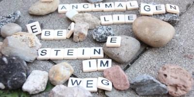 """Hier sieht man Buchstaben auf Steinen, die einen Spruch ergeben. Der Spruch lautet """"manchmal liegen eben Steine im Weg"""""""