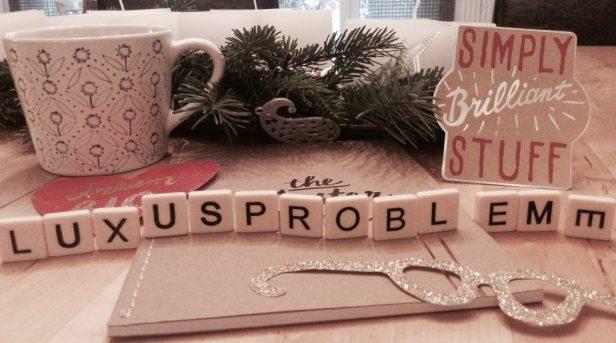 """Hier ist ein Notizbuch zu sehen, auf dem """"The Masterplan"""" steht. Daneben eine Teetasse. Zwischen dekorativen Stickern stehen die Buchstaben """"Luxusprobleme"""""""