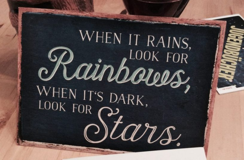 "Hier ist ein Bild von einer Postkarte zu sehen, auf der die englische Aufschrift: ""When it rains, look for rainbows, when its dark, look for stars"" steht"