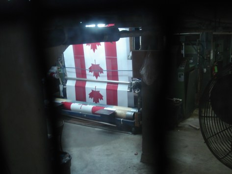 An evening image of a Flying Colours printing press printing Canadian flags