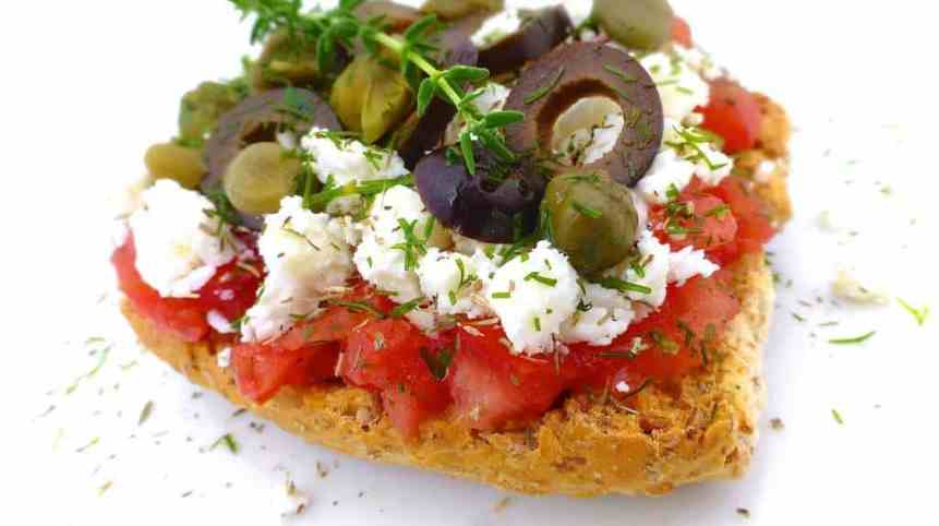 Traditional Cretan ntakos: a rusk sandwich toast topped with the freshest ingredients such as tomatoes, feta cheese, capers and olives!