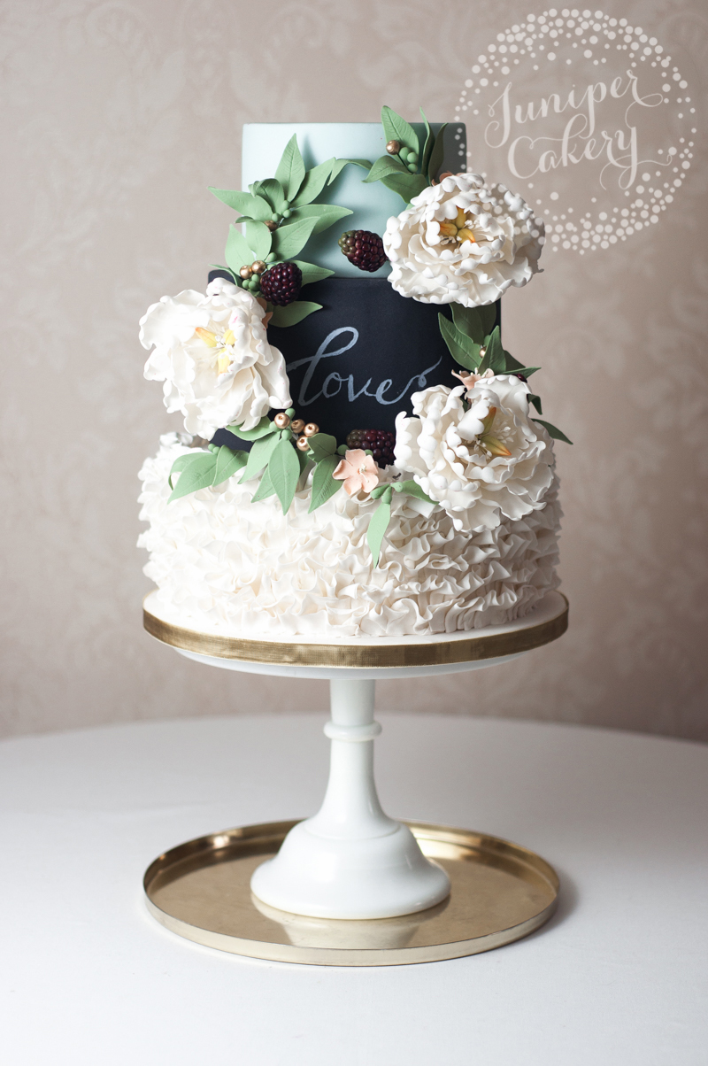 Rustic chalkboard wedding cake with white open peonies, peach blossoms and seeded eucalyptus by Juniper Cakery