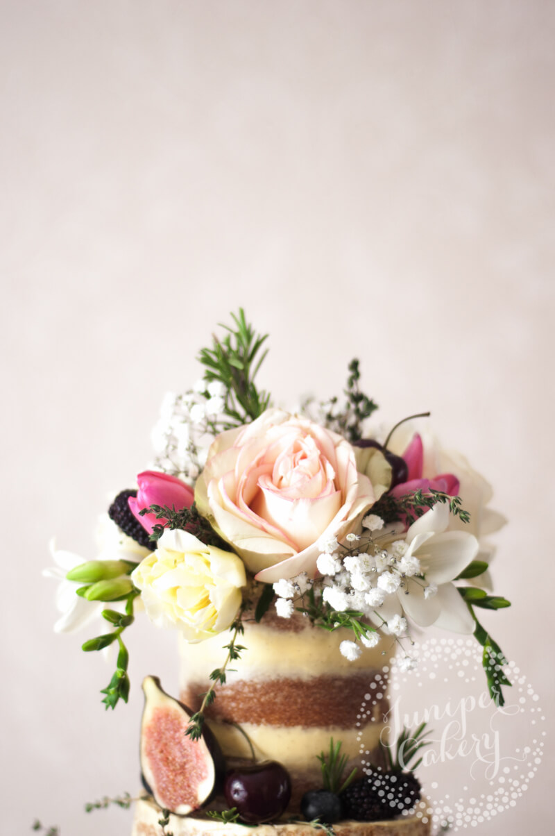 Stunning semi-naked wedding cake with florals by Juniper Cakery