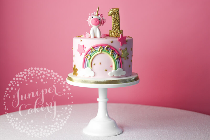 Cute pink unicorn birthday cake with rainbow by Juniper Cakery