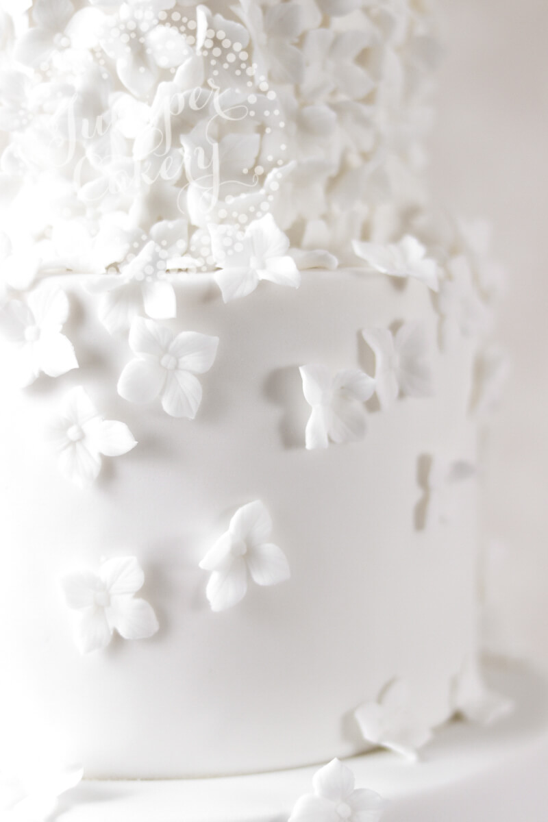 A flurry of white sugar blossoms on a wedding cake by Juniper Cakery