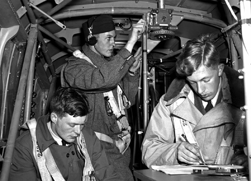 Sgt E.M. Romilly, RCAF, W.H. Betts, RAAF, and J.A. Mahoud, RAF, practicing navigation techniques on board an Anson from the No 1 Air Navigation School, Rivers, Manitoba, 4th June, 1941.