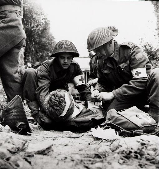 Un blessé de la 3ème Division d'infanterie canadienne reçoit les premiers soins de membres de la station de secours du régiment, avec l'aide de l'aumônier de cette unité, près de Caen en Normadie, 15 juillet 1944.