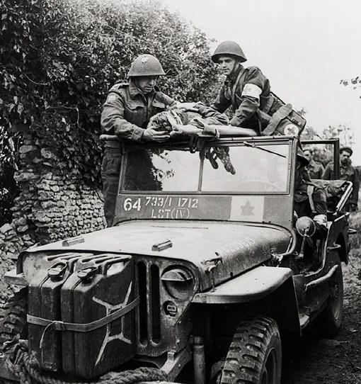 Un blessé de la 3ème Division d'infanterie canadienne est évacué par les membres de la station de secours du régiment, avec l'aide de l'aumônier de cette unité, près de Caen en Normadie, 15 juillet 1944.
