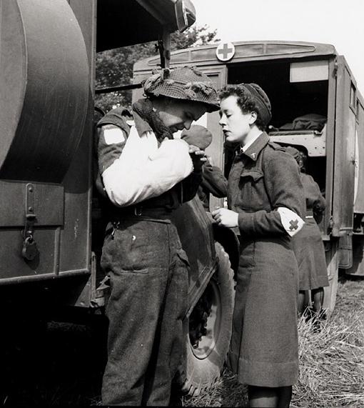 L'infirmière M.F. Giles vérifie les pansements du soldat F. Madore, à l'aérodrome de la RCAF en France, 16 juin 1944. Près du front, les infirmières apportaient un présence réconfortante aux hommes qu'elles traitaient.