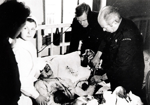 Dr. Norman Bethune, assisted by Henning Sorensen, performing a transfusion during the Spanish Civil War, 1935-1938.