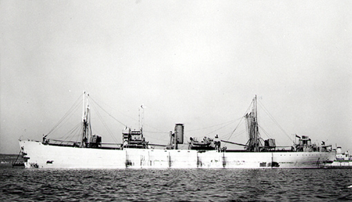 At anchor, unloaded SS Elk Island Park awaits loading orders. Delivered 6 June 1943 by Montreal-based United Shipyards, she is equipped with torpedo nests secured to booms stowed vertically against the mainmast.