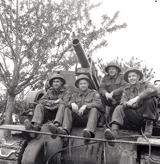 Gnr. Donald Harper, Gnr. Dalton Keyes, Gnr. George Lindop (Ganonoque, ON) and Gnr. Andrew Fairhurst (Englehart, ON), 14th Field Regiment, RCA, seating on a Priest self-propelled gun in Normandy, 20 June 1944.