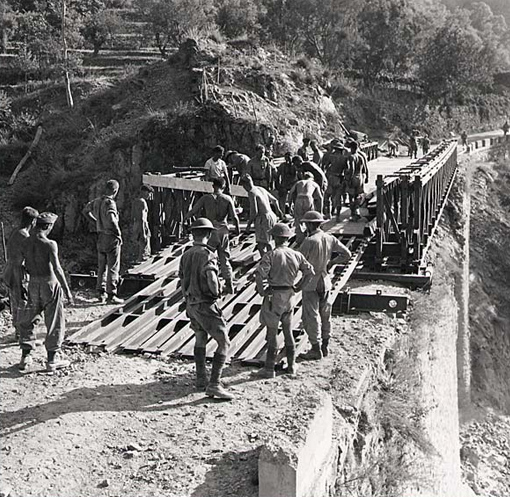 In the mountains of Calabria, the progression of tanks and armoured vehicles was often slowed down as many bridges had been destroyed by the retreating German forces. The 1st Field Company of the Royal Canadian Corps of Engineers setting up a Bailey bridge over a ravine of the Straorini River, September 4th, 1943.