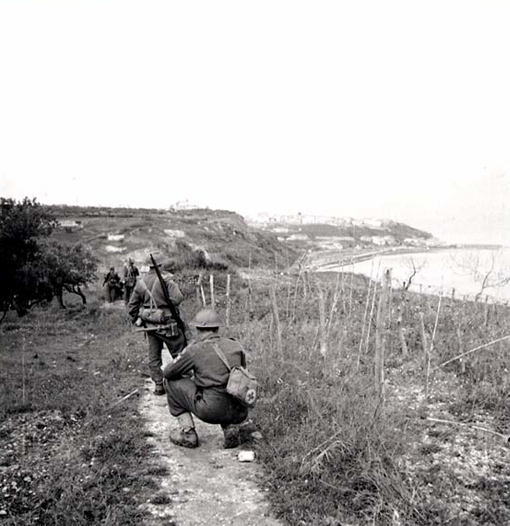 "Company ""B"" of the Seaforth Highlanders moving along a mined coastal path December 21st, 1943; Ortona can be seen in the distance."