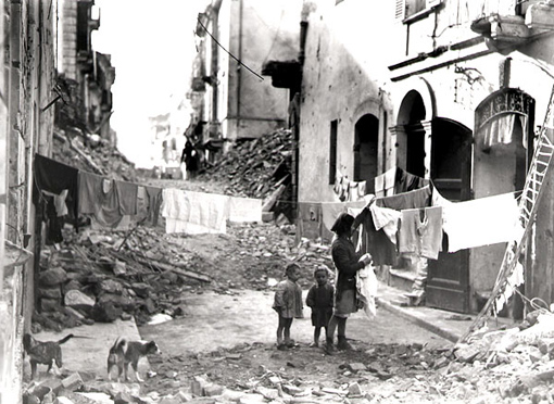 The battle over, the population resumes its daily activities in a city in ruins; a young woman hanging clothes to dry amid the rubble, January 13th, 1944.