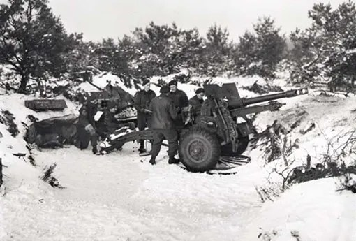 "Members of ""B"" Troop, 5th Field Regiment, firing 25-pounder near Malden, Holland, 1 February 1945. From left to right: Sergeant Jack Brown, Bdr. Joe Wilson, Gunners Lyle Ludwig, Bill Budd, George Spence, and Bill Stewart."