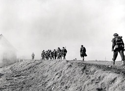 Les fusiliers du Régiment de la Chaudière avancent sur une digue lors du nettoyage des terres inondées de la région de Clèves en Allemagne, le 10 février 1945.
