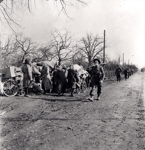 Canadian infantrymen passing German refugees near Xanten, Germany, March 9th, 1945.
