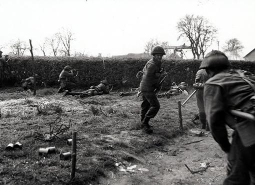 Près d'une ferme hollandaise, des fusiliers du South Saskatchewan Regiment s'accroupissent pour faire feu à travers une haie, à proximité du canal Oranje aux Pays-Bas, le 12 avril 1945.