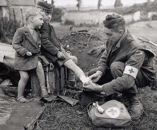 Lance Corporal W.J. Curtis, Royal Canadian Army Medical Corps, fixes the burned leg of a French boy, while his young brother looks on. Between Colomby-sur-Thaon and Villons-les-Buissons, Normandy, 19 June 1944.