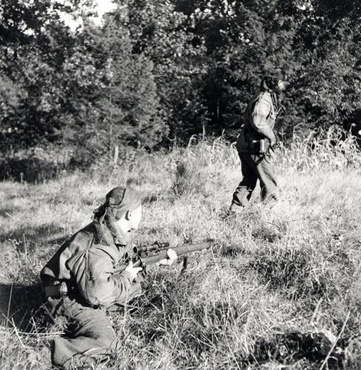 Le caporal S. Kormendy couvre le sergent H.A. Marshall, un éclaireur des Calgary Highlanders, alors qu'il avance en terrain découvert près de Kapellen (Belgique) le 6 octobre 1944.