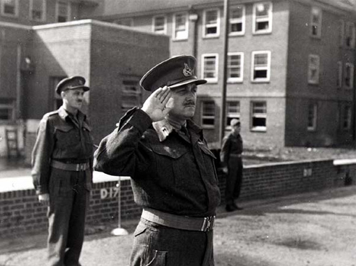Major-General Charles Foulkes standing at attention during an inspection of Canadian troops in England, May 12th, 1944