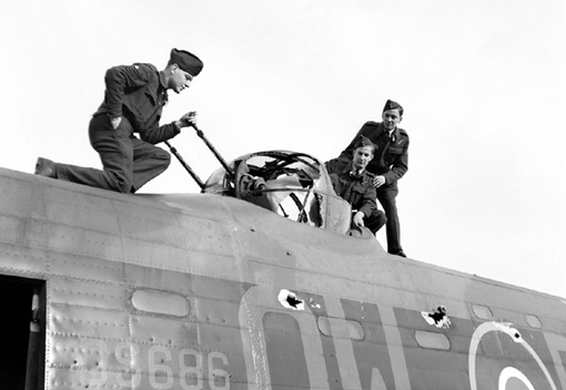 This No 426 Squadron Lancaster was hit by over one hundred machine-gun bullets or shell fragments during a raid on Leipzig, October 25th, 1943. F/Sgt G.V. Andrew and F/O Rod James Dunphy and Jimmy H. Dodge assess the damage to the dorsal turret of the aircraft.