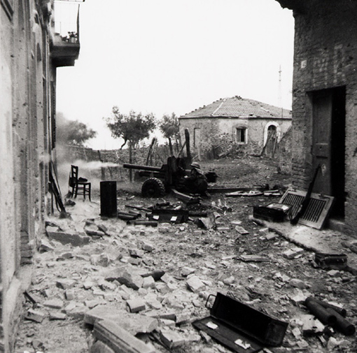Soldier firing 6-pounder anti-tank gun at the end of a street in Ortona, Italy, 21 December 1943.