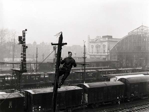 Signalman J. Bennett of the 1st Canadian Railway Telegraph Company installing wire on pole in station yards, Louvain, Belgium, 6 January 1945.