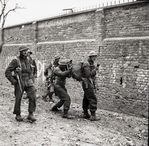 Edmonton Regiment soldiers use walkie-talkie during advance in Ortona, Italy, 21 December 1943. Carrying it is Lance Corporal W. D. Smith. Talking into it is Private W. L. Waske.