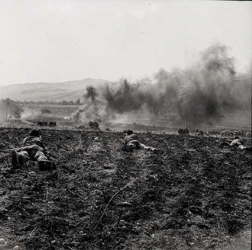 Princess Patricia's Canadian Light Infantry in action over a rise, near Valguarnera, Sicily, 20 July 1943. Enemy heavy trucks are ablaze in the distance.