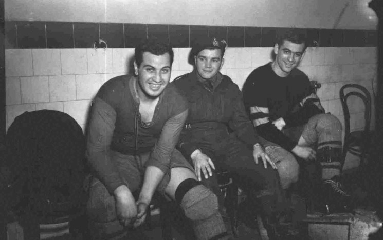 Three Canadian hockey players sit in their locker room in 1945