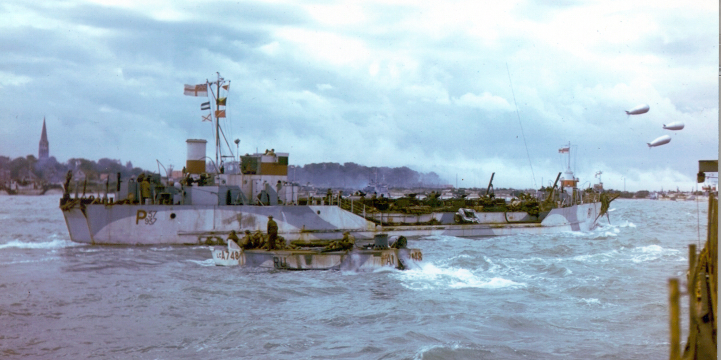 Colour photograph. A Landing Craft Tank (LCT), loaded with Sherman tanks belonging to 2nd Canadian Armoured Brigade, sails along the coast off Bernières-sur-Mer. The Church steeple in the centre of the town is visible at the left edge of the photo. A much smaller Landing Craft Assault (LCA) putters past in front of the LCT. Source: Library and Archives Canada CT 305 / Courtesy of the Juno Beach Centre Association