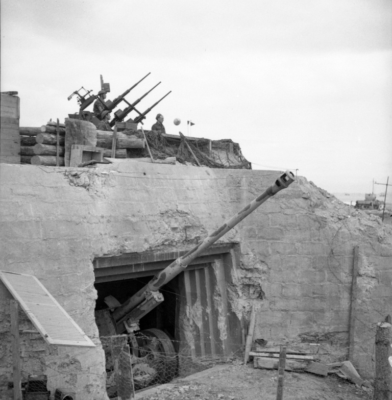 Black and white photograph. A German bunker at the entrance to the Courseulles-sur-Mer harbour has been transformed by the Canadians into a light anti-aircraft position, 14 July 1944. This bunker, which contains an 88 mm gun, was captured by the Regina Rifles on D-Day. Source: Canada. Dept. of National Defence / Library and Archives Canada / PA-140856 / Courtesy of the Juno Beach Centre Association